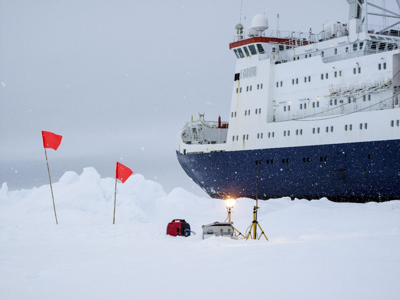 Dataloggers measuring environmental parameters near a research icebreaker over an ice floe in Antarctica
