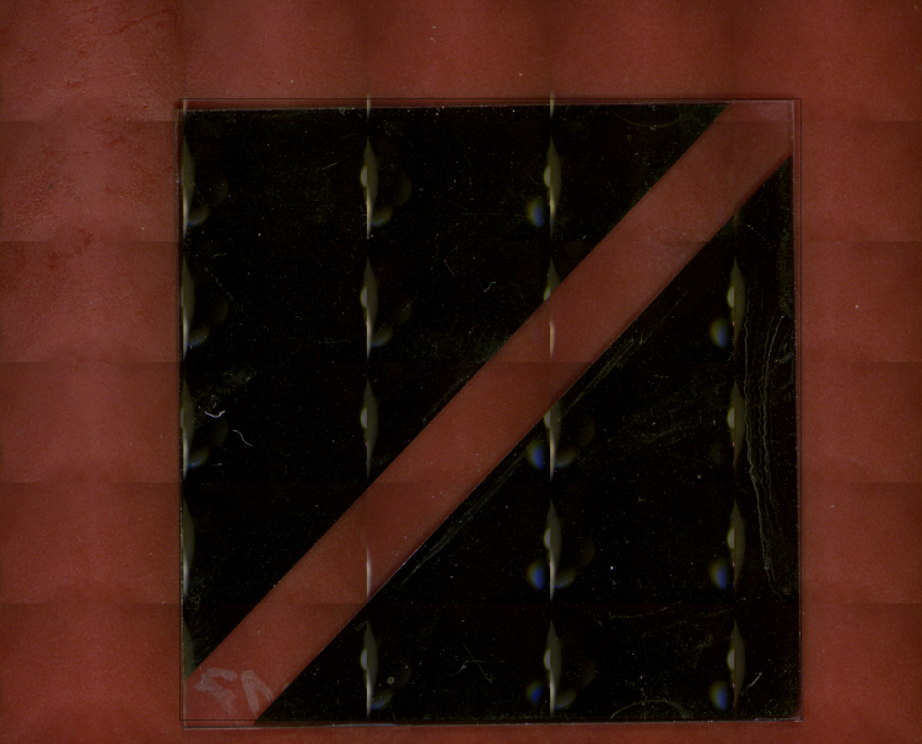 The sample, two electrodes on a glass substrate, is a test device for photoinduced electrolysis.  It is composed of a bi-metal monolayer with a concentration gradient along the surface. The glass substrate is coated by magnetron sputtering of a dual Cu-Al-target.